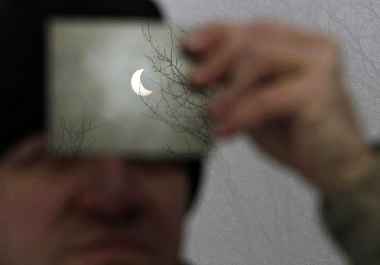 A man watches a partial solar eclipse through a filter in Galyateto, some 100 km (62 miles) east of Budapest, January 4, 2011. REUTERS/Bernadett Szabo (HUNGARY - Tags: ENVIRONMENT IMAGES OF THE DAY)