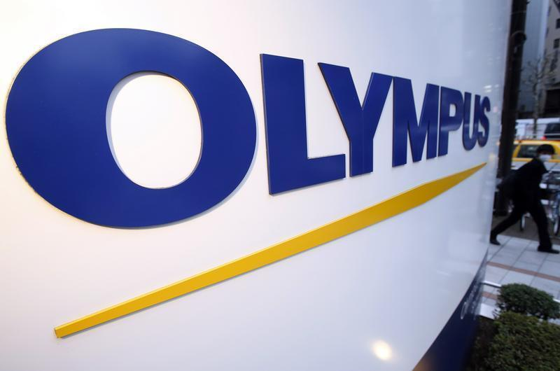 A man passes a logo of Japan's Olympus outside the company showroom in Tokyo