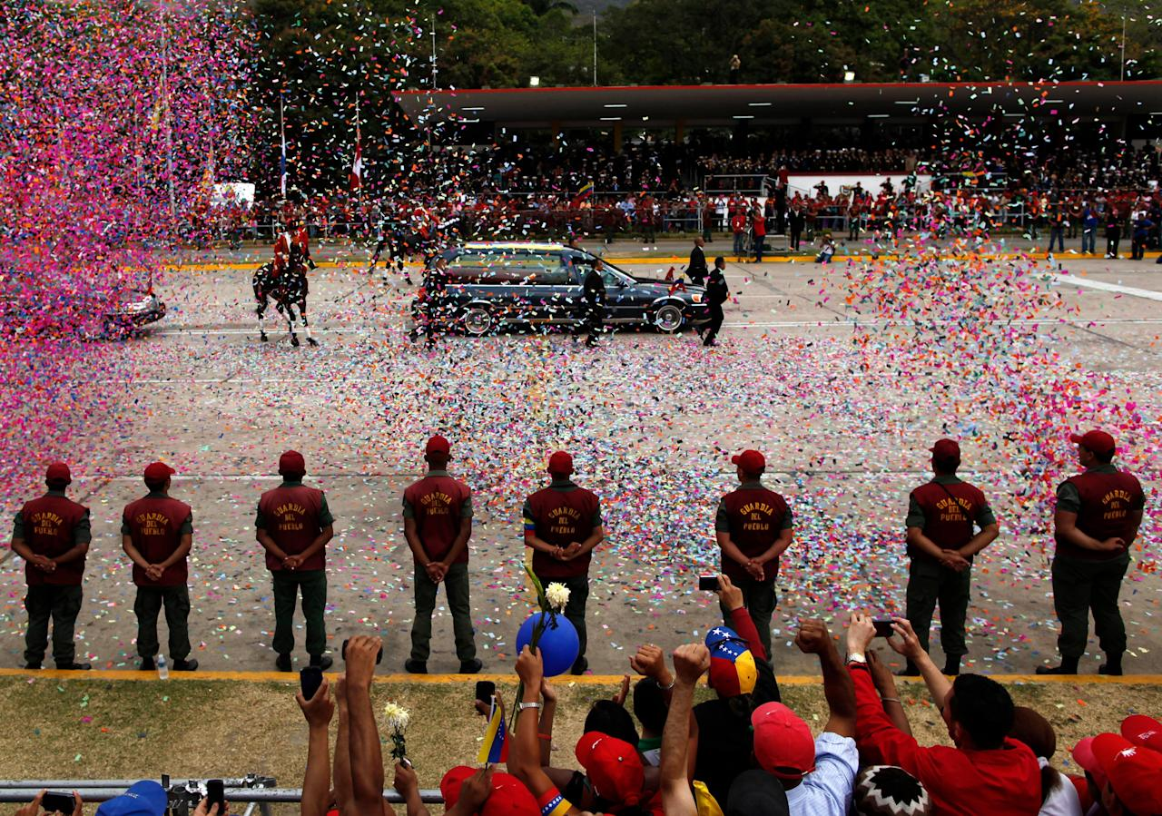 Confetti falls around the hearse carrying the coffin that contains the remains of Venezuela's late President Hugo Chavez, in a funeral procession, in Caracas, Venezuela, Friday, March 15, 2013. Chavez's body is being transferred Friday from the military academy where it has been lying in state to the military museum that will serve as his final resting place. Venezuelans lined up to bid their last farewell to Hugo Chavez on Friday. Chavez was 58 when he died of an undisclosed type of cancer on March 5. (AP Photo/Rodrigo Abd)