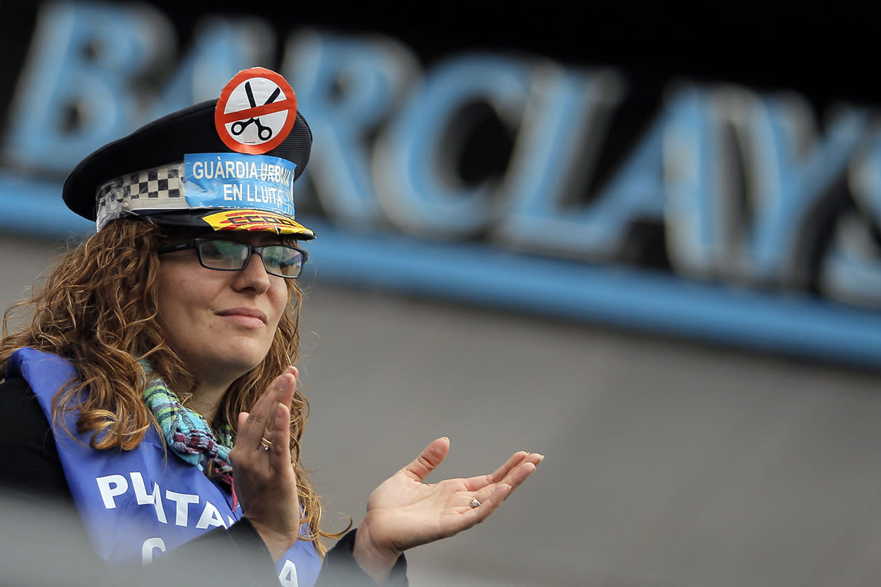 "A Barclays bank banner is seen as a police officer  wears a hat with a banner reading, ""Urban guards in conflict"" during a protest  against government's austerity measures and the elimination of their Christmas bonus pay, one of 14 paychecks that most Spanish civil servants get each year, in Madrid."