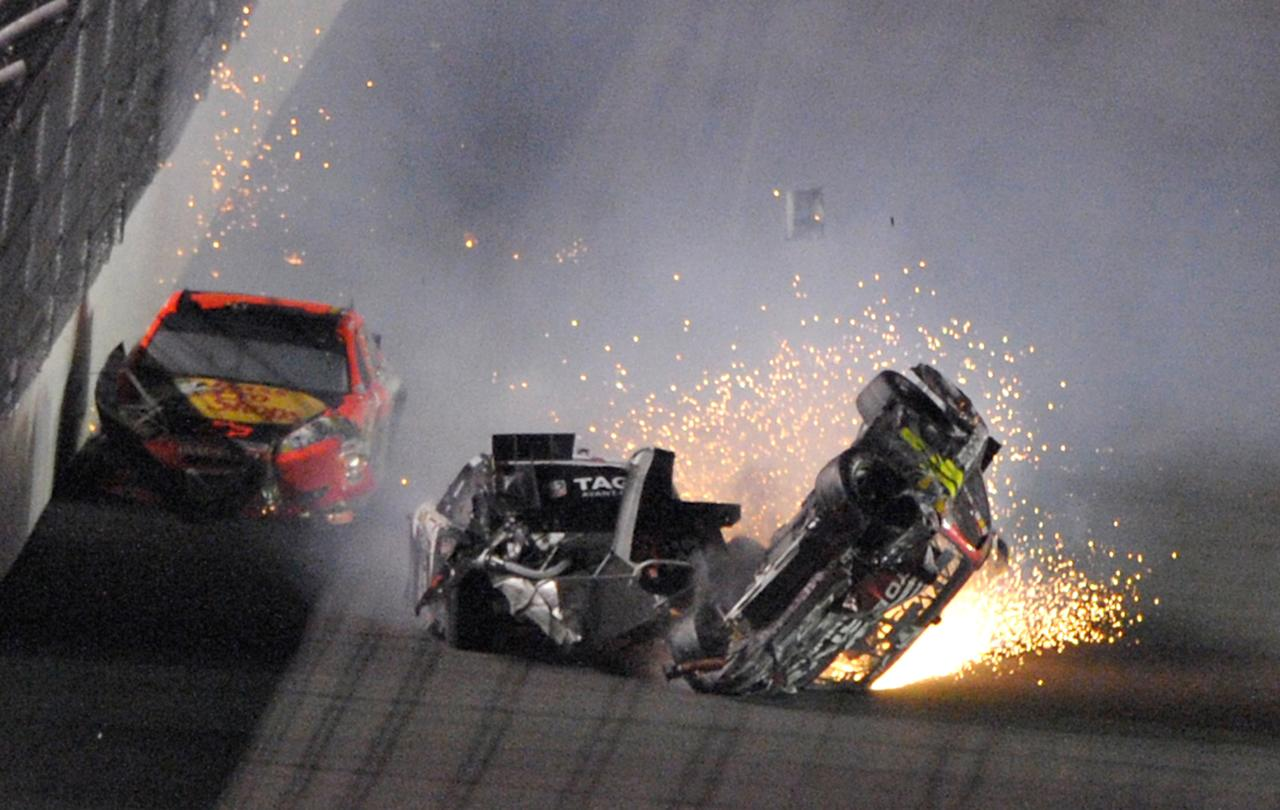 Jeff Gordon's car, right, slides on its side after a colliding with the vehicles of Kurt Busch, center, and Jamie McMurray, left, during the NASCAR Budweiser Shootout auto race at Daytona International Speedway, Saturday, Feb. 18, 2012, in Daytona Beach, Fla. (AP Photo/Phelan M. Ebenhack)