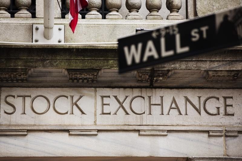 A street sign for Wall Street hangs in front of the New York Stock Exchange