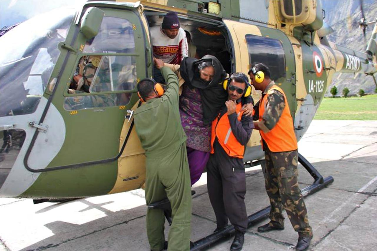 """In this photograph received from the Indian Army on June 20, 2013, members of the Indian Defence Forces assist an evacuee out of a helicopter following flash floods in the northern Uttarakhand state. India's military battled on June 20 to reach villages and towns cut off by flash floods and landslides in the country's north as officials warned at least 1,000 people may have been killed. AFP PHOTO/INDIAN ARMY   ----EDITORS NOTE---- RESTRICTED TO EDITORIAL USE - MANDATORY CREDIT -  """"AFP PHOTO/INDIAN ARMY"""" - NO MARKETING NO ADVERTISING CAMPAIGNS - DISTRIBUTED AS A SERVICE TO CLIENTS -----"""