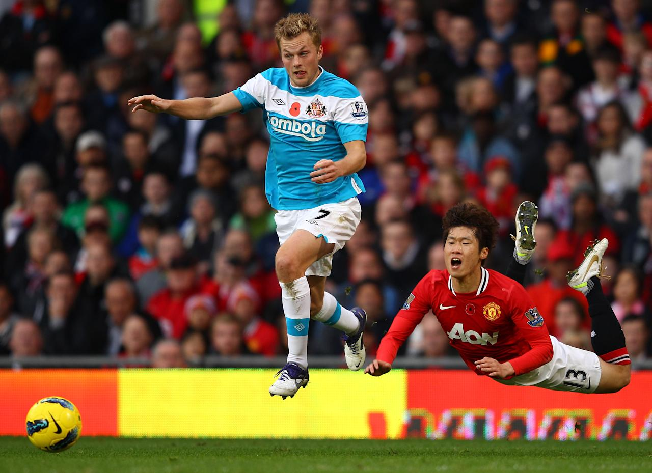 MANCHESTER, ENGLAND - NOVEMBER 05:  Ji-Sung Park of Man Utd is brought down by Sebastien Larsson and Michael Turner of Sunderland during the Barclays Premier League match between Manchester United and Sunderland at Old Trafford on November 5, 2011 in Manchester, England.  (Photo by Richard Heathcote/Getty Images)