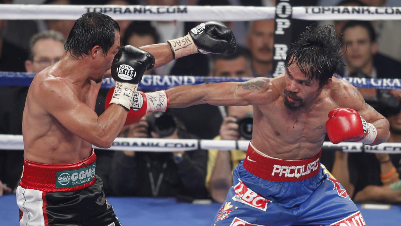 Juan Manuel Marquez, left, and Manny Pacquiao exchanges punches round during a WBO welterweight title fight, Saturday, Nov. 12, 2011, in Las Vegas. Pacquiao won by majority decision. (AP Photo/Isaac Brekken)
