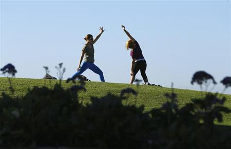 Women do yoga in a public park next to the beach in Del Mar, California
