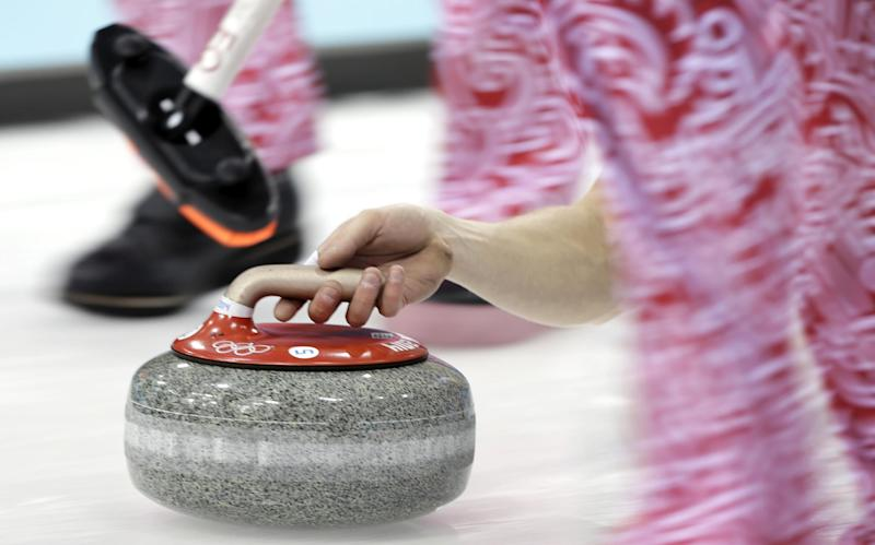 Russia's Evgeny Arkhipov delivers the rock during the men's curling competition against China at the 2014 Winter Olympics, Saturday, Feb. 15, 2014, in Sochi, Russia