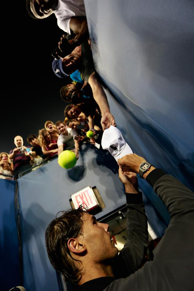 NEW YORK, NY - SEPTEMBER 02: Rafael Nadal of Spain signs autographs for fans following his victory over Philipp Kohlschreiber of Germany during their fourth round men's singles match on Day Eight of the 2013 US Open at the USTA Billie Jean King National Tennis Center on September 2, 2013 in New York City. (Photo by Chris Trotman/Getty Images for the USTA)
