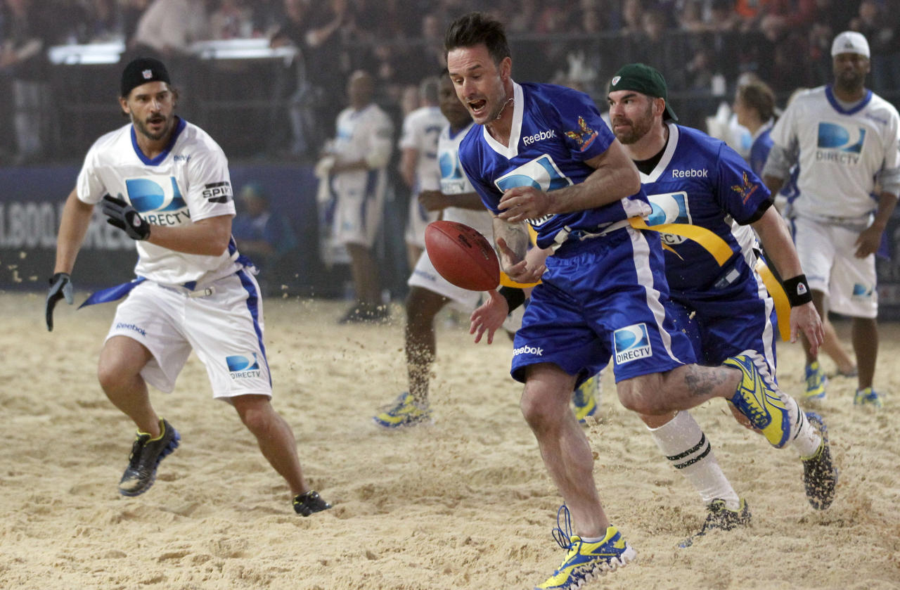 Actor David Arquette, center, drops a pass fellow actors Brandon Molale, right, and Joe Manganiello, left, look on during the Celebrity Beach Bowl, part of the festivities for NFL football's Super Bowl XLVI, Saturday, Feb. 4, 2012, in Indianapolis. †(AP Photo/Jeff Roberson)