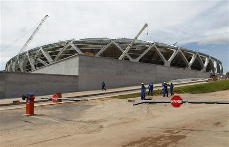 Workers stand outside the Arena Amazonia soccer stadium after a worker fell to his death in Manaus