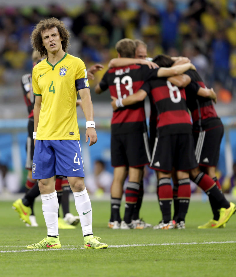 Brazil's David Luiz (4) reacts after Germany's Sami Khedira scored his side's fifth goal during the World Cup semifinal soccer match between Brazil and Germany at the Mineirao Stadium in Belo Horizonte, Brazil, Tuesday, July 8, 2014. (AP Photo/Andre Penner)