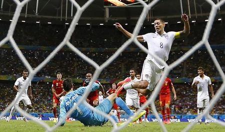 Clint Dempsey of the U.S. is tackled by Belgium's goalkeeper Courtois during extra time in their 2014 World Cup round of 16 game at the Fonte Nova arena in Salvador