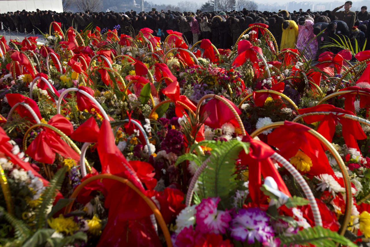 Offerings of flowers are lined up as North Koreans bow in front of bronze statues of the late leaders Kim Il Sung and Kim Jong Il to pay their respects in Pyongyang, North Korea on Saturday, Feb. 16, 2013. North Koreans turned out to commemorate what would have been the 71th birthday of Kim Jong Il who died on Dec. 17, 2011. (AP Photo/David Guttenfelder)