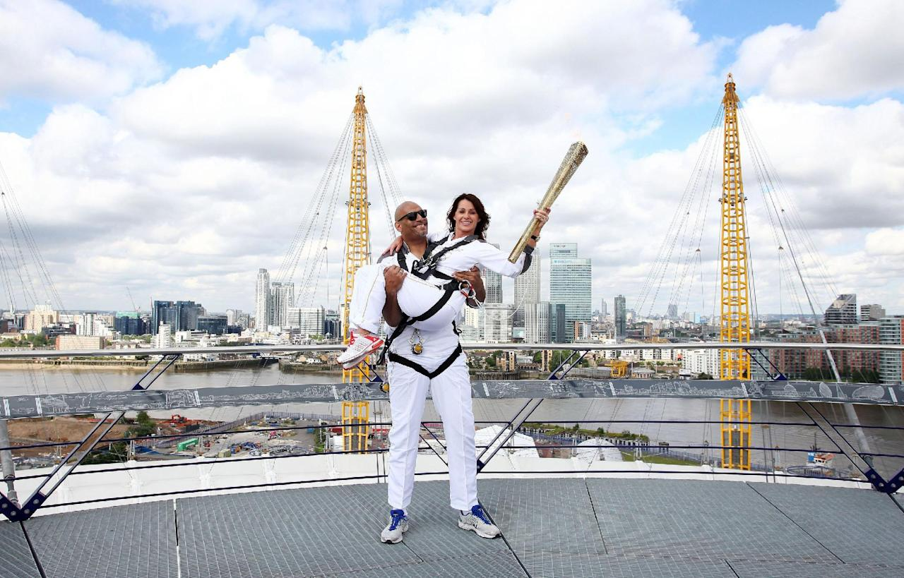 The photo provided by LOCOG shows torchbearers Nadia Comaneci, right, and John Amaechi posing with the Olympic Torch on the viewing platform of the North Greenwich Arena, London, Saturday, July 21, 2012. (AP Photo/LOCOG, Gareth Fuller)