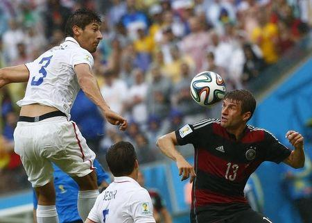 Gonzalez of the U.S. jumps for the ball with Germany's Mueller during their 2014 World Cup Group G soccer match at the Pernambuco arena in Recife