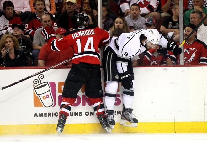NEWARK, NJ - JUNE 02: Drew Doughty #8 of the Los Angeles Kings draws contact from Adam Henrique #14 of the New Jersey Devils during Game Two of the 2012 NHL Stanley Cup Final at the Prudential Center on June 2, 2012 in Newark, New Jersey.  (Photo by Elsa/Getty Images)