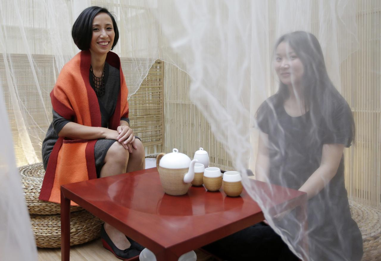 Jiang Qiong Er (L), Shang Xia's artistic director and chief executive, poses during a Chinese tea ceremony in Paris September 11, 2013. Shang Xia, the Chinese-born brand backed by French luxury goods group Hermes, opened its first shop outside its home market in Paris on Wednesday to test appetite among non-Chinese customers for its handcrafted products. The brand is trying to build a business centred on the revival of traditional Chinese crafts such as porcelain, cashmere felt and furniture, that were all but nearly destroyed by China's proletarian Cultural Revolution. REUTERS/Jacky Naegelen (FRANCE - Tags: FASHION BUSINESS)
