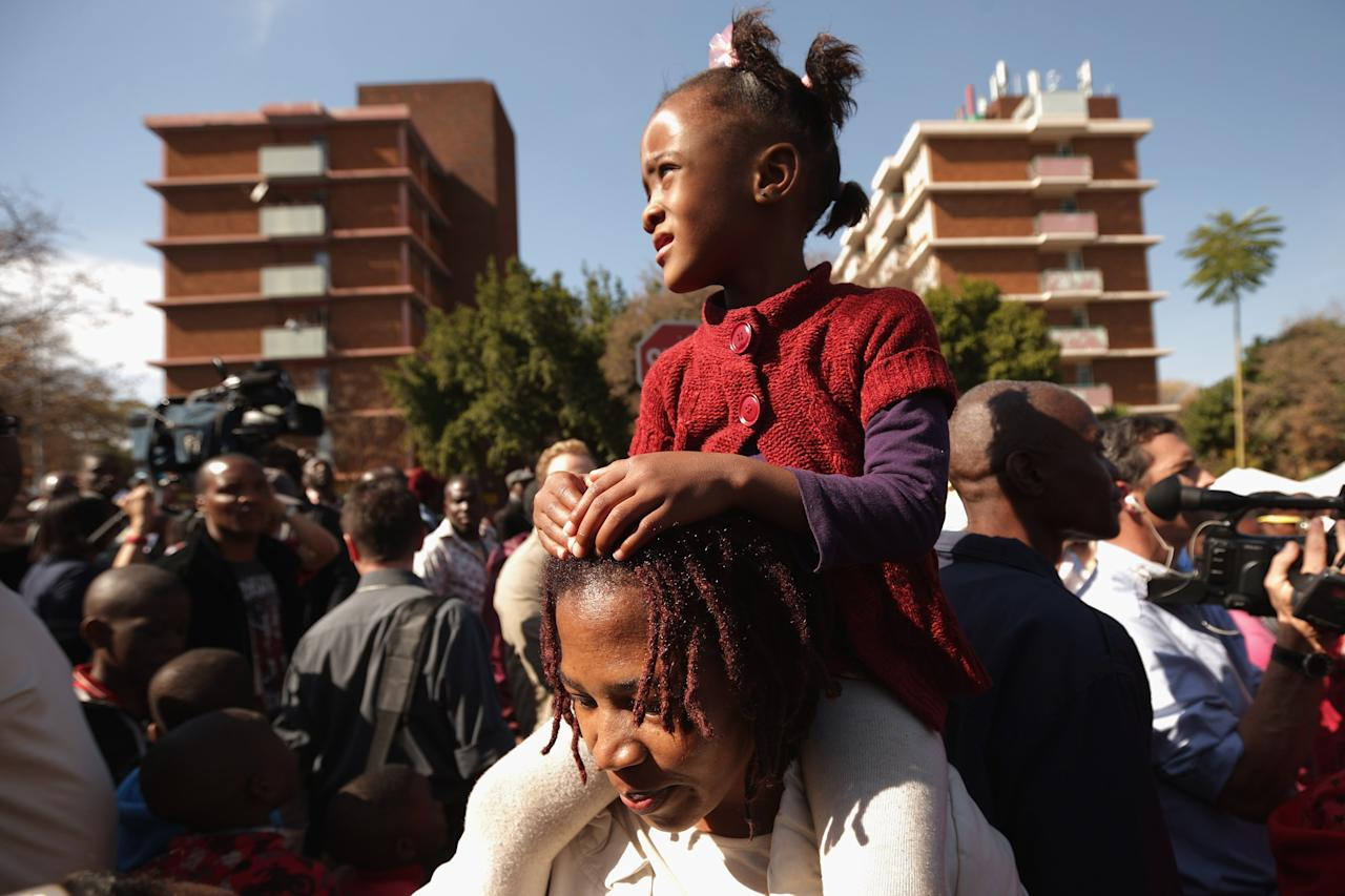 PRETORIA, SOUTH AFRICA - JUNE 27:  A girl sits on her mother's shoulders while navigating the crowd outside the Mediclinic Heart Hospital where Mandela is being treated for a recurring lung infection June 27, 2013 in Pretoria, South Africa. Family members and President Jacob Zuma have visited Mandela in the hospital today.  (Photo by Chip Somodevilla/Getty Images)