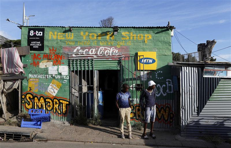 Residents stand outside a spaza convienience shop in Cape Town's Imizamo Yethu township