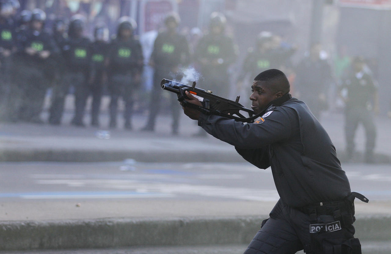 A police officer aims his weapon during clashes with Anti-World Cup demonstrators near Maracana stadium where the final World Cup game is taking place in Rio de Janeiro, Brazil, Sunday, July 13, 2014. For the final match between Argentina and Germany, authorities deployed the largest security detail in Brazil's history. (AP Photo/Leo Correa)