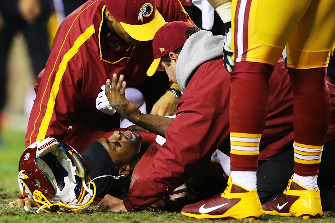 LANDOVER, MD - JANUARY 06:  Robert Griffin III #10 of the Washington Redskins receives attention after he was injured on a bad snap in the fourth quarter against the Seattle Seahawks during the NFC Wild Card Playoff Game at FedExField on January 6, 2013 in Landover, Maryland.  (Photo by Al Bello/Getty Images)
