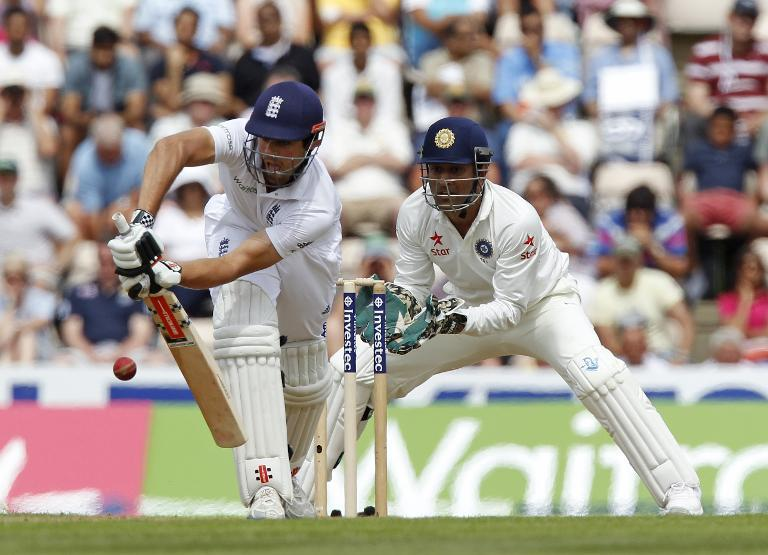 England's Captain Alastair Cook (left) hits a shot watched by India's Captain and wicketkeeper MS Dhoni during their first day of the third Test match at the Ageas Bowl ground in Southampton on July 27, 2014