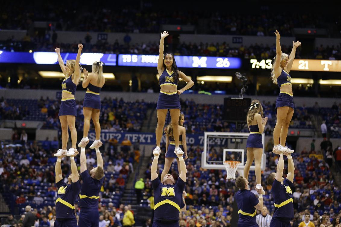 Michigan cheerleaders perform during the first half of an NCAA Midwest Regional semifinal college basketball tournament game against the Tennessee Friday, March 28, 2014, in Indianapolis. (AP Photo/Michael Conroy)