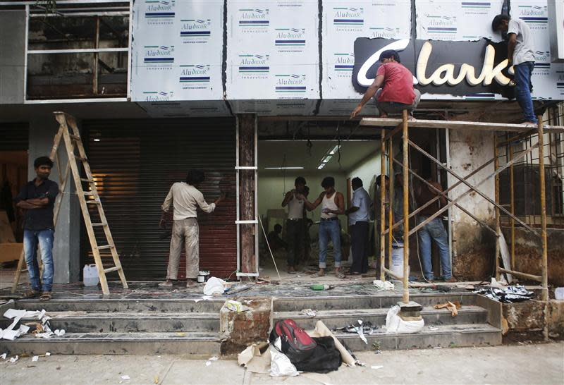Men work at the site of a new shoe store on a street in Mumbai