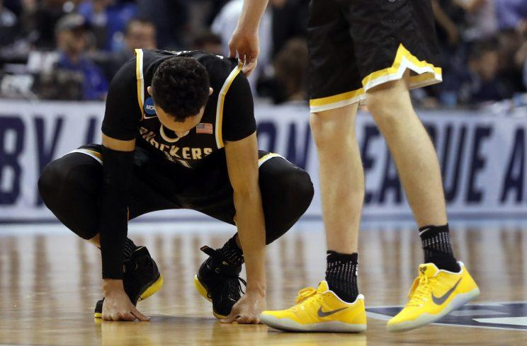 Wichita State's Landry Shamet is consoled by a teammate following a 65-62 loss to Kentucky on Sunday. (AP)