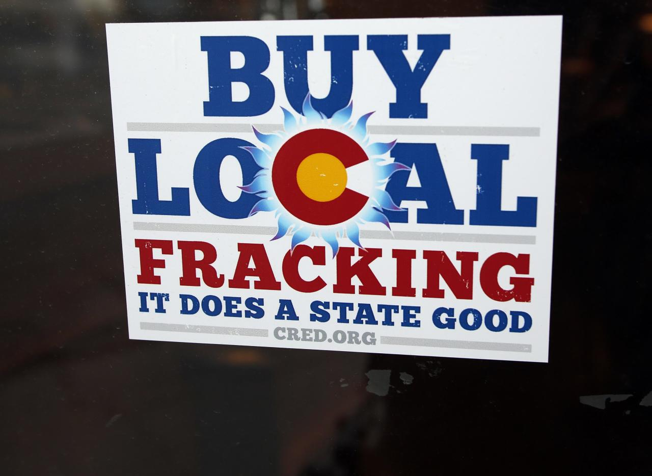 """A sign supporting fracking on the doorway at Mama's Restaurant in Parachute, Colorado, December 10, 2014. The economy of Parachute, with a current population of approximately 1000 people, was devastated when thousands of workers lost their jobs on """"Black Sunday"""" in 1982, after Exxon terminated the Colony Shale Oil Project. The current rise of hydraulic fracking in natural gas retrieval has given a cautious hope to the town's inhabitants, who know that market demand brings both boom and bust. Picture taken December 10, 2014.  REUTERS/Jim Urquhart (UNITED STATES  - Tags: ENERGY BUSINESS)"""