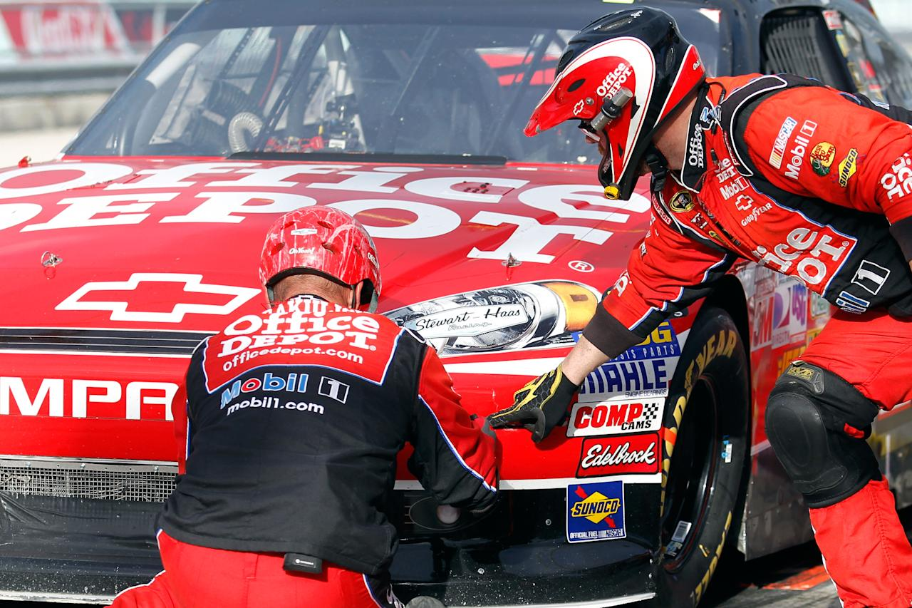 HOMESTEAD, FL - NOVEMBER 20:  Crew members work on the #14 Office Depot/Mobil 1 Chevrolet driven by Tony Stewart after Stewart pits after sustaining damage to the front end of his car during the start of the NASCAR Sprint Cup Series Ford 400 at Homestead-Miami Speedway on November 20, 2011 in Homestead, Florida.  (Photo by Todd Warshaw/Getty Images for NASCAR)