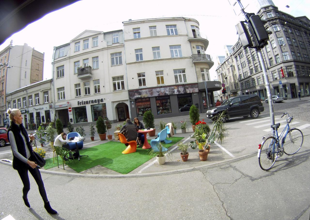 A woman walks past people participating in a PARK(ing) Day event in Riga, September 20, 2013. The event aims to transform metered parking spaces into temporary public places to call attention to the need for more urban open spaces and discuss the creation and allocation of public spaces, according to organizers. REUTERS/Ints Kalnins (LATVIA - Tags: SOCIETY)