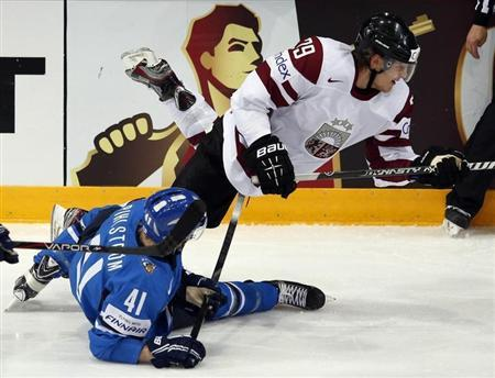 Latvia's Freibergs trips over Finland's Pihlstrom during their 2013 IIHF Ice Hockey World Championship preliminary round match at the Hartwall Arena in Helsinki