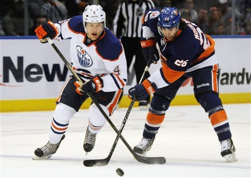 Edmonton Oilers' Taylor Hall, left, and the New York Islanders' Nino Niederreiter go for the puck in the first period of the NHL hockey game in Uniondale, New York, Saturday, Dec. 31, 2011. (AP Photo/Henny Ray Abrams)