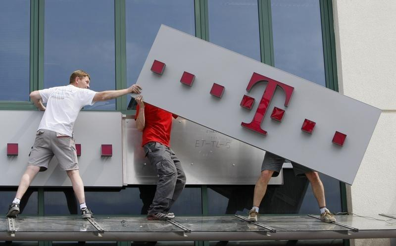 File photo of T-Mobile logo being positioned on a shop front