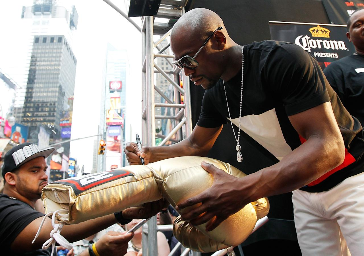 NEW YORK, NY - JUNE 24: Floyd Mayweather signs autographs following a news conference at the Pedestrian Walk in Times Square on June 24, 2013 in New York City. Floyd Mayweather and Canelo Alvarez are scheduled to fight September 14 at the MGM Grand in Las Vegas, Nevada to unifty their junior middleweight world titles. (Photo by Mike Stobe/Getty Images)