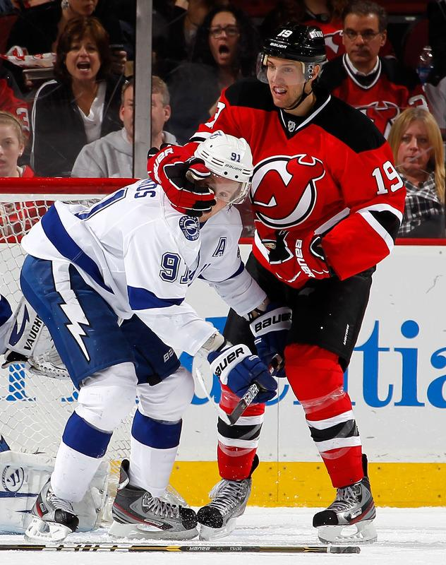 NEWARK, NJ - MARCH 29:  Travis Zajac #19 of the New Jersey Devils takes a handful of the helmet of Steven Stamkos #91 of the Tampa Bay Lightning during the second period of an NHL hockey game at Prudential Center on March 29, 2012 in Newark, New Jersey.  (Photo by Paul Bereswill/Getty Images) *** BESTPIX ***