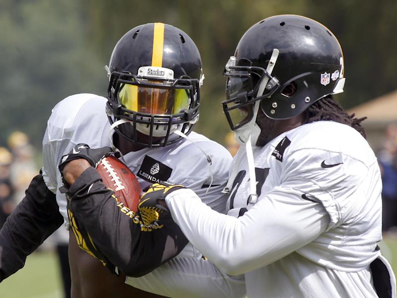 Pittsburgh Steelers running back LeGarrette Blount, right, tries to strip the ball from fellow Steelers running back Le'Veon Bell in a drill  during a combined NFL football training camp session with the Buffalo Bills in Latrobe, Pa. on Wednesday, Aug. 13, 2014