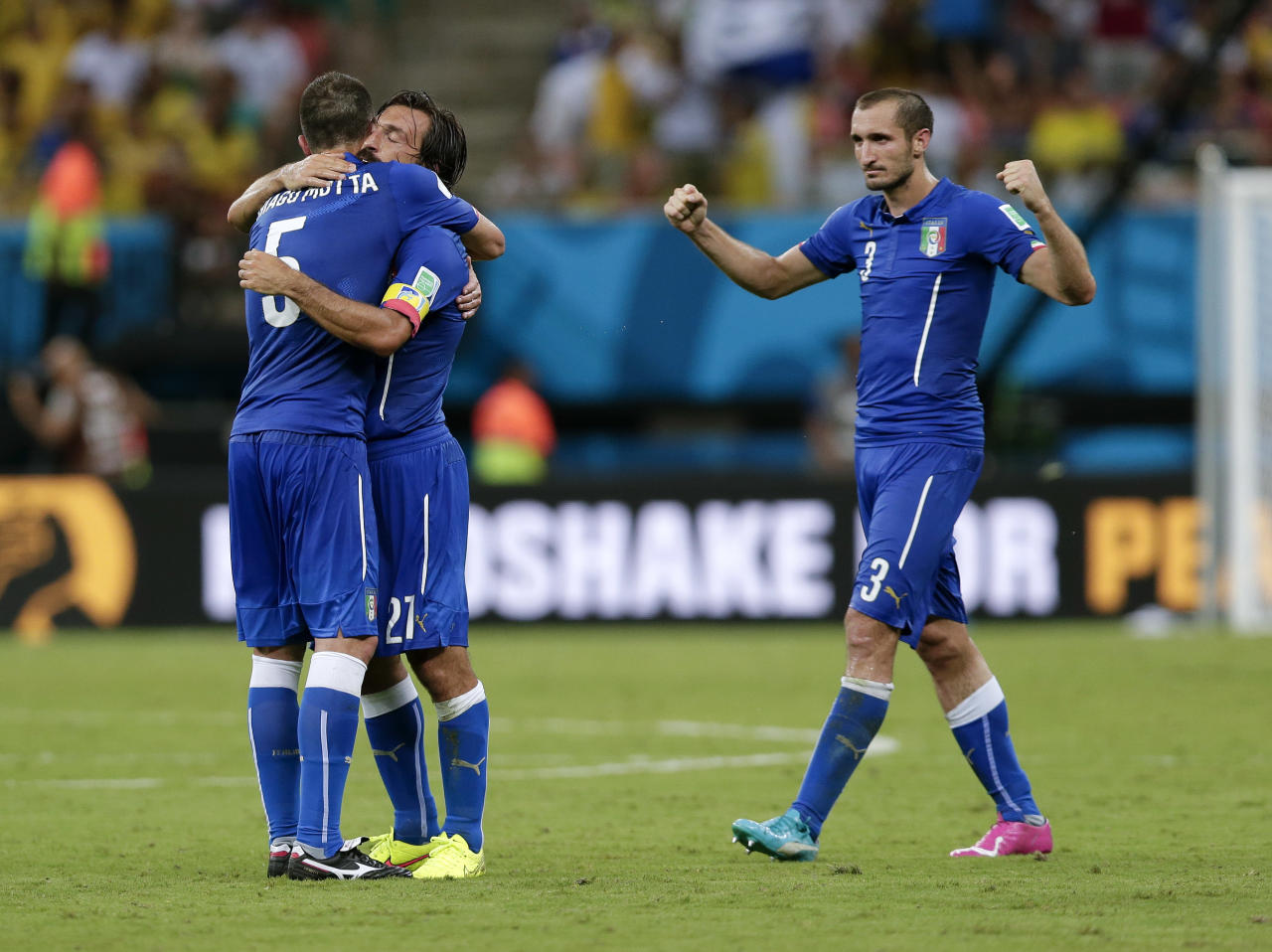 Italy's Thiago Motta (5) hugs Andrea Pirlo (21) as Giorgio Chiellini (3) joins them after defeating England 2-1 in their group D World Cup soccer match at the Arena da Amazonia in Manaus, Brazil, Saturday, June 14, 2014. (AP Photo/Marcio Jose Sanchez)