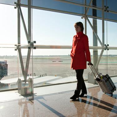 Businesswoman-at-aiport-traveling-with-trolley-in-red-coat_web
