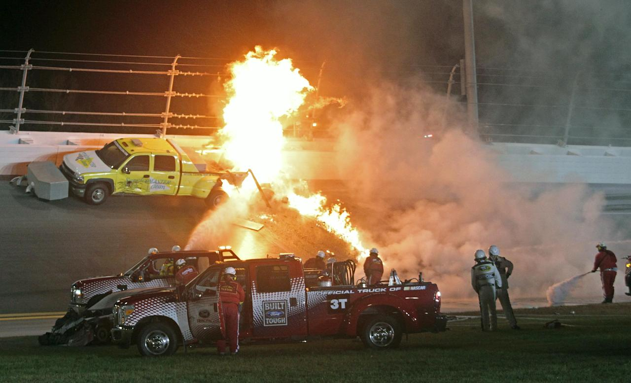 Emergency workers try to put out a fire after Juan Pablo Montoya's car struck the truck during the NASCAR Daytona 500 auto race at Daytona International Speedway in Daytona Beach, Fla., Monday, Feb. 27, 2012. (AP Photo/Bill Friel)