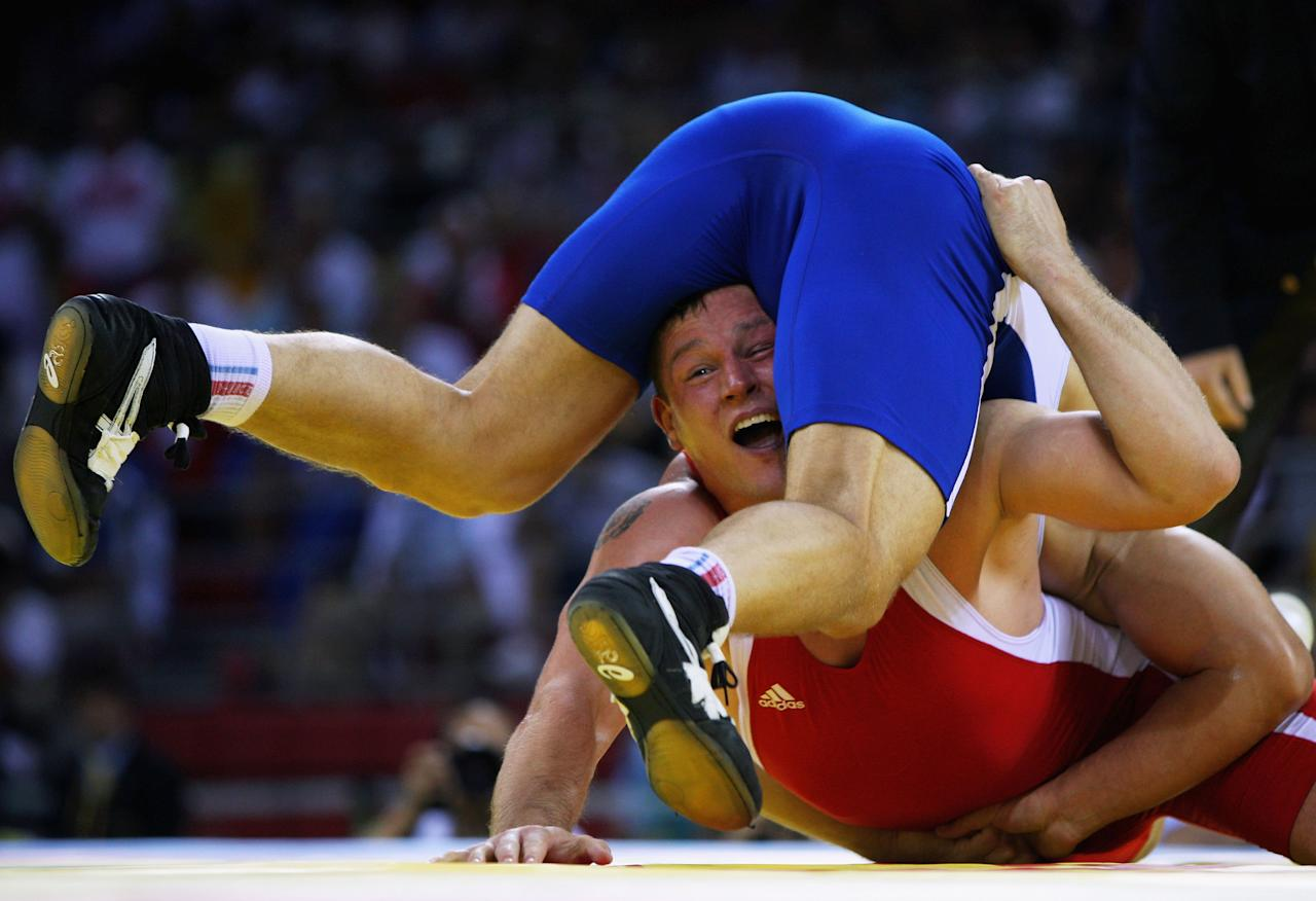 BEIJING - AUGUST 14:  Aslanbek Khustov (blue) of Russia and Mirko Englich (red) of Germany compete in the Men's Greco-Roman 96kg gold medal bout at the China Agriculture University Gymnasium during Day 6 of the Beijing 2008 Olympic Games on August 14, 2008 in Beijing, China.  (Photo by Ezra Shaw/Getty Images)
