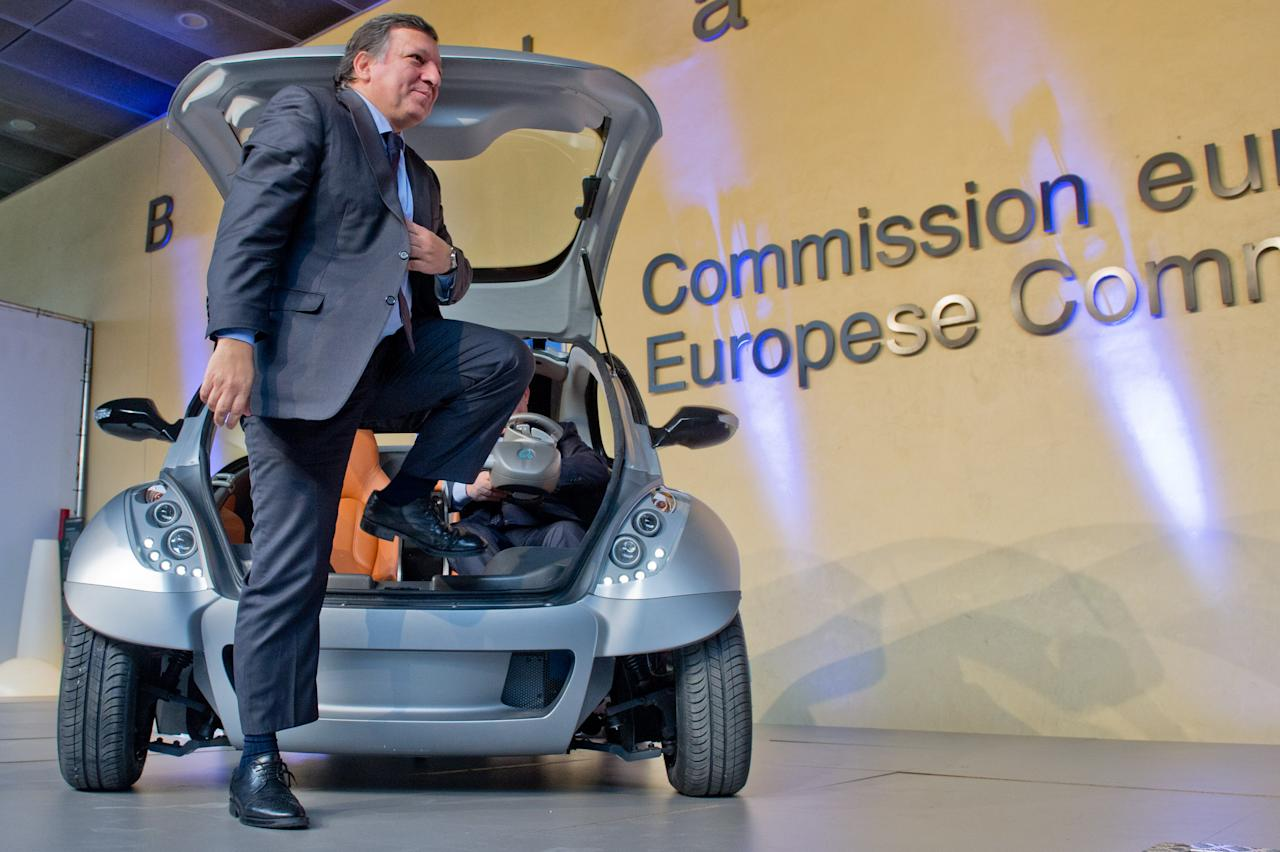 "BRUSSELS, BELGIUM - JANUARY 24:  EU Commission President Jose Manuel Barroso steps out of the first prototype of the HIRIKO electric car, during the global launch of Hiriko Driving Mobility at the EU Commssion headquarters on January 24, 2012 in Brussels, Belgium. The electronic, eco-friendly vehicle will be manufactured in deprived areas of cities who take up Hiriko's ""social purpose"" model. Malmo in Sweden has already signed up to trial Hiriko with Berlin, Barcelona, Vitoria-Gasteiz (the second largest Basque city), San Francisco, and Hong Kong expected to follow suit.  (Photo by Geert Vanden Wijngaert/Getty Images)"
