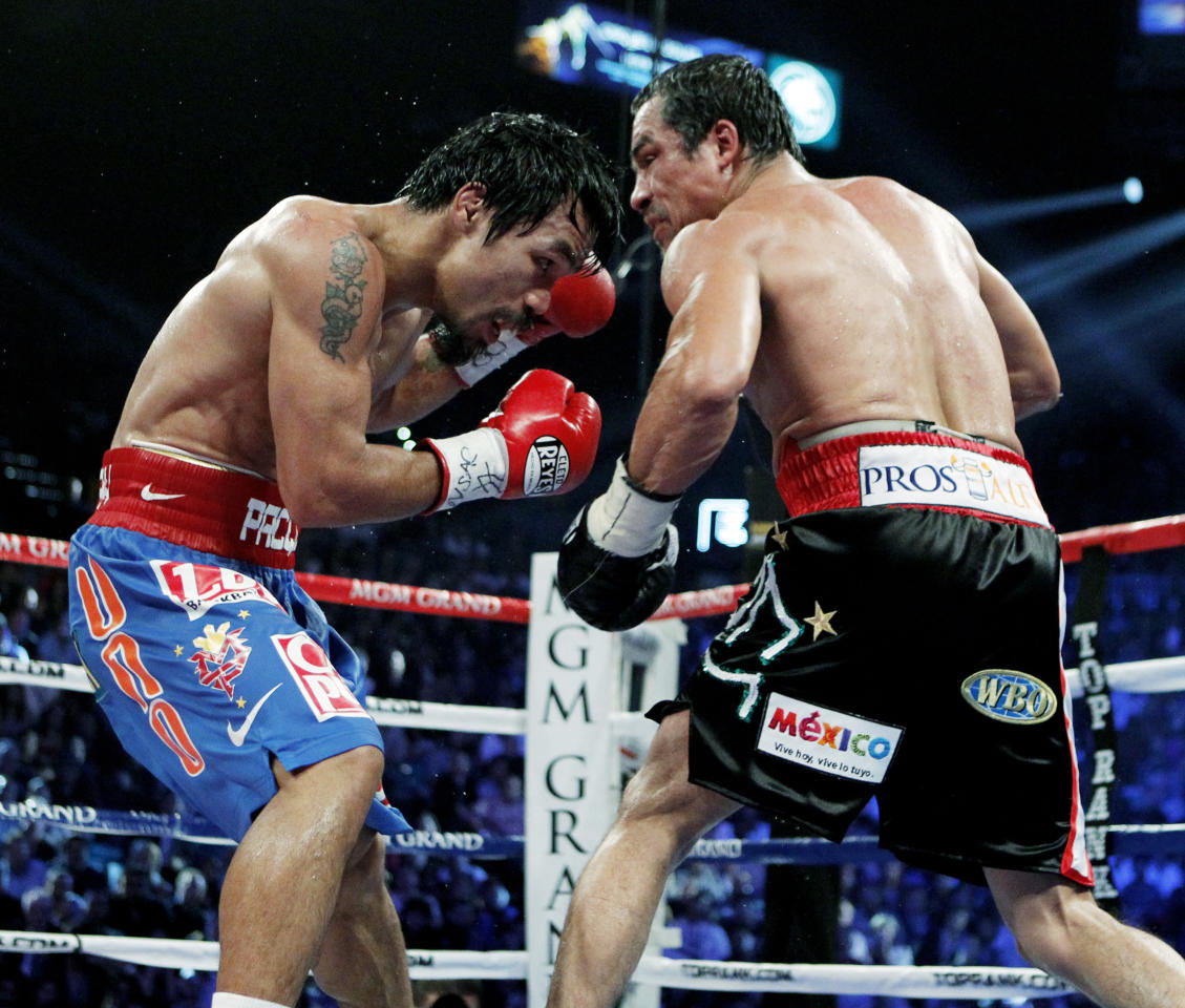 Mexico's Juan Manuel Marquez, right, hits Manny Pacquiao, of the Philippines, during a WBO welterweight title fight Saturday, Nov. 12, 2011, in Las Vegas. (AP Photo/Jae C. Hong)