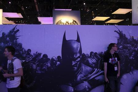 "People stand near WB Games' ""Batman: Arkham Origins"" signage at E3, the Electronic Entertainment Expo, in Los Angeles, California, June 11, 2013. REUTERS/David McNewÊÊ"