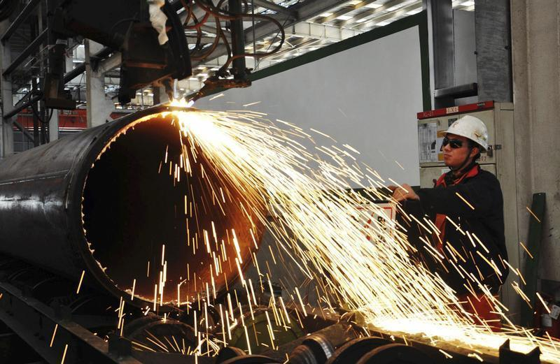 A worker operates a machine to cut a pipeline at a factory in Qingdao