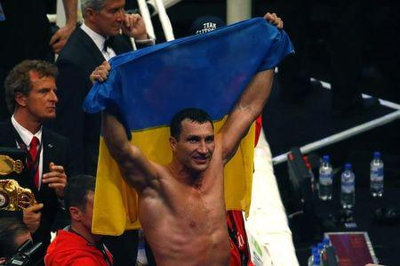World heavyweight boxing champions Klitschko of Ukraine celebrates with an Ukrainian flag after defeating Australian challenger Leapai during their WBO heavyweight title fight in Oberhausen