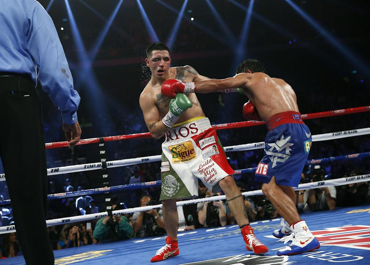 Manny Pacquiao, from the Philippines, right, lands a left to Brandon Rios of the United States during their WBO international welterweight title fight Sunday, Nov. 24, 2013, in Macau. Pacquiao defeated Rios by unanimous decision on Sunday to take the WBO international welterweight title and return to his accustomed winning ways after successive defeats.   (AP Photo/ Vincent Yu)