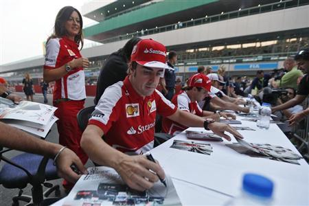 Ferrari F1 driver Alonso signs autographs for fans at the Buddh International Circuit in Greater Noida