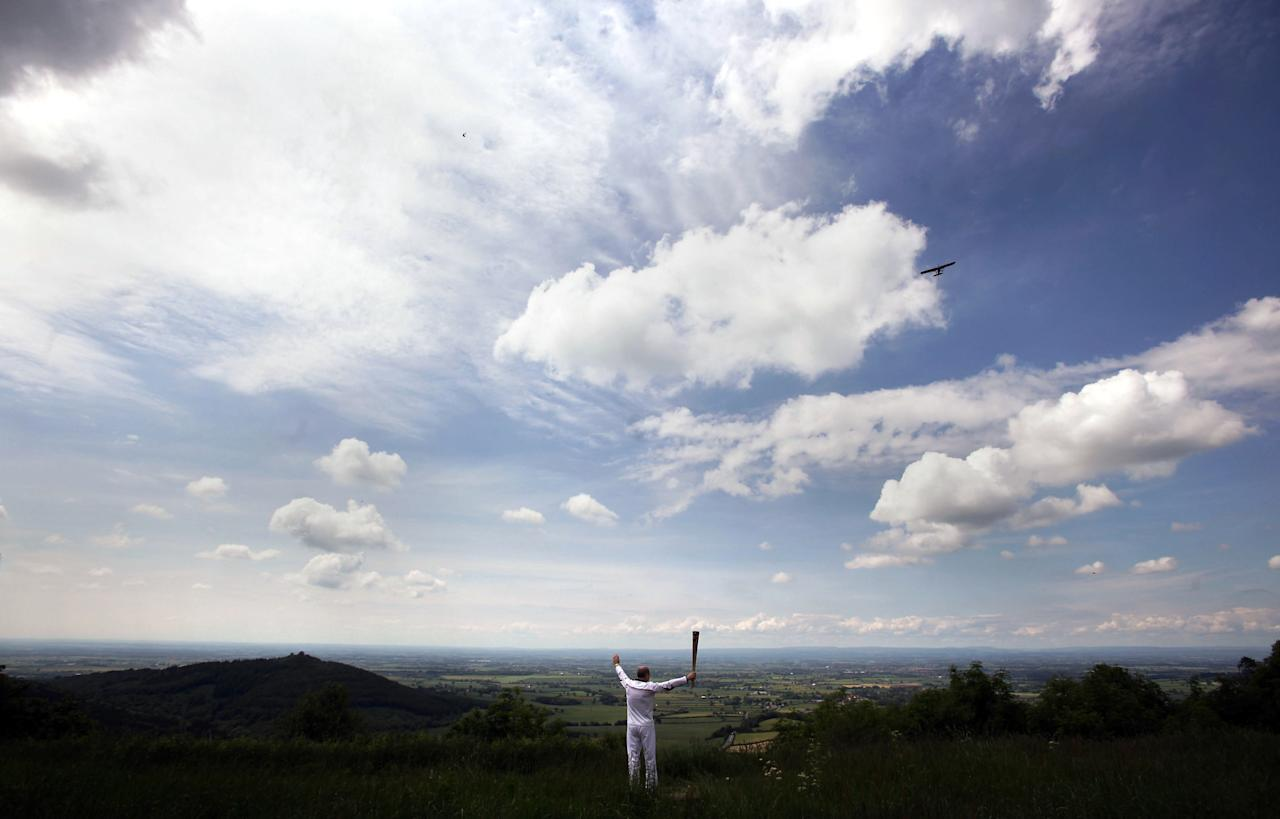 YORK, UNITED KINGDOM - JUNE 20:  In this handout image provided by LOCOG, Torchbearer 011 Eugene Perry carries the Olympic Flame at Sutton Bank, part of the North Yorkshire Moors National Park, with Vale of York in background  on June 20, 2012 in York, England. The Olympic Flame is now on day 33 of a 70-day relay involving 8,000 torchbearers covering 8,000 miles.  (Photo by LOCOG via Getty Images)